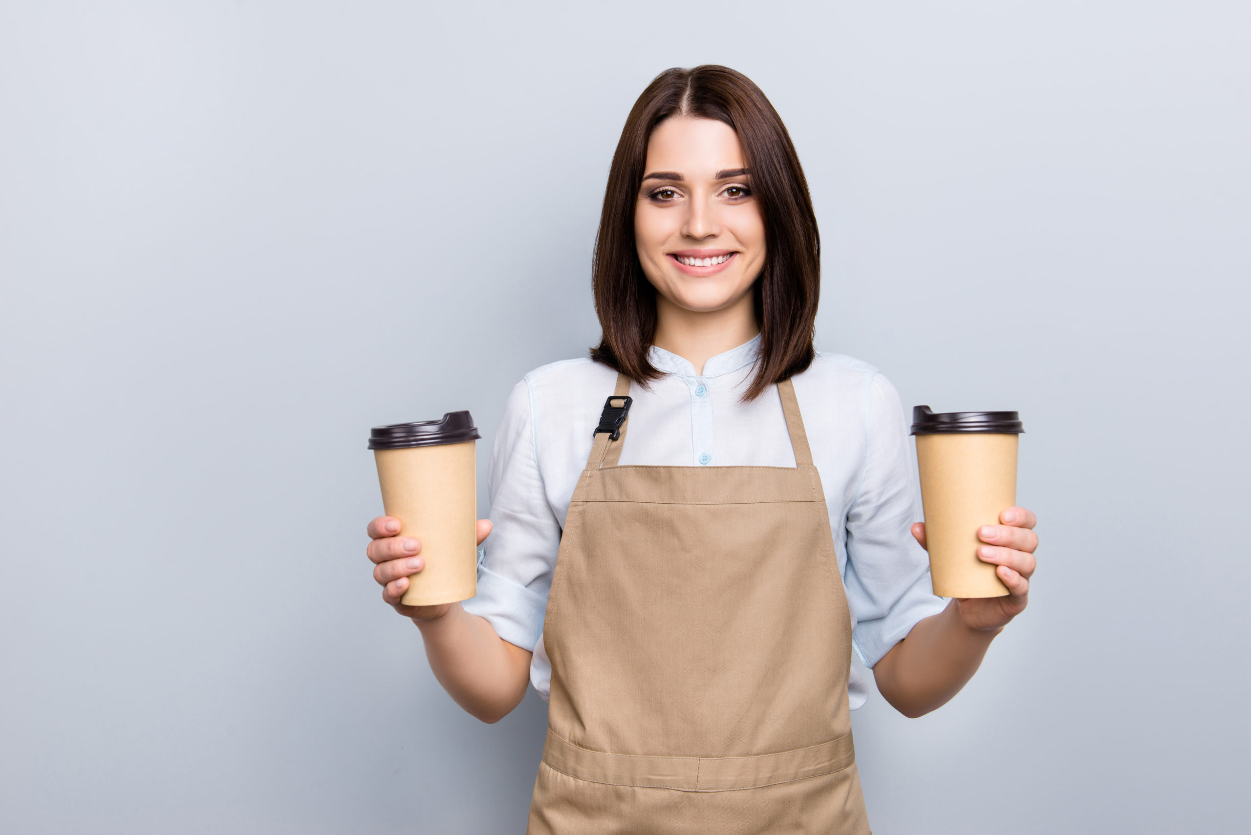 Barista hold two cups of coffee, representing the doubling of orders for the past two years.