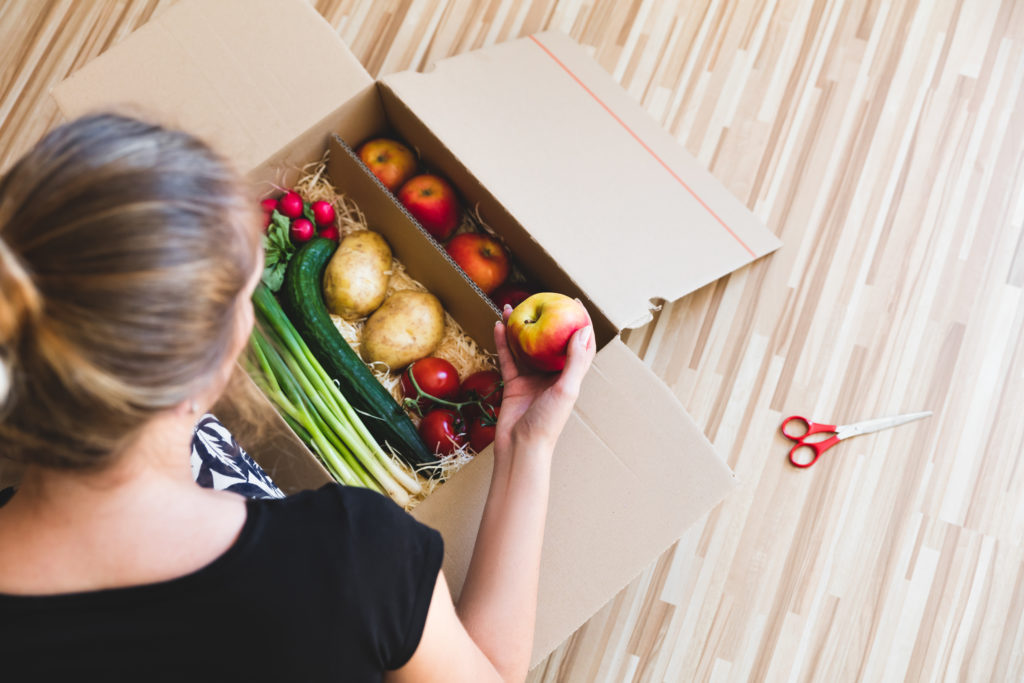 Woman opens a box of vegetables.